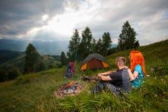 Соедините сидеть на зеленой траве около лагерного костера, шатров, рюкзаков Стоковое Изображение