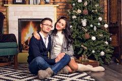 Соедините сидеть на комнате рождества пола живущей Стоковые Изображения