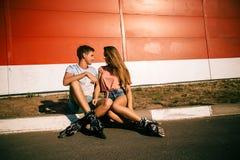 Соедините сидеть на обочине на красной стене Стоковые Изображения