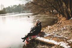 Соедините сидеть на пристани на замороженном озере смотря один другого Стоковая Фотография RF