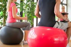 Соедините тренировку в спортзале с гантелями перед зеркалом сидя на fitballs Стоковое фото RF