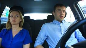 Соедините управлять в автомобиле, человеке и езде женщины совместно в автомобиле через улицы города и взгляда вокруг сток-видео