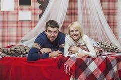 Соедините человека и женщины в спальне на кровати с одеялом Стоковое Фото