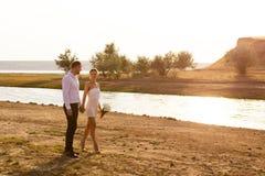 Соедините человека и женщины идя совместно на предпосылку захода солнца Стоковая Фотография
