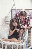 Соедините человека и женщины с smartphone дома на качании стула стоковое фото