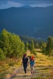 Соедините hikers при рюкзаки держа руки, идя в горы Стоковая Фотография RF