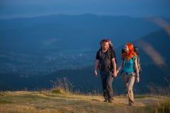 Соедините hikers при рюкзаки держа руки, идя в горы Стоковая Фотография