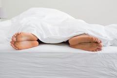 Соединяет ноги вставляя вне из-под одеяла Стоковое Изображение RF