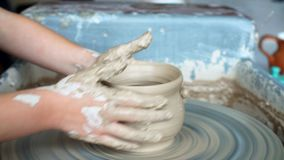 Создавать глиняный горшок горшечник Мастерская глины Глина на приборе оригинал Руки работая на гончарне катят, формирующ глиняный видеоматериал