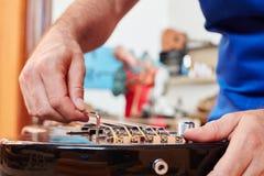 Создатель гитары регулирует электрическую гитару Стоковое Изображение