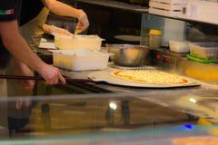 Создатель пиццы пока подготавливающ испечь пиццу все еще сегодня в pizzerias древесин-увольнятьая печь предпочтена стоковая фотография