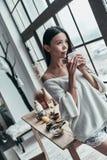 Созерцание утра Привлекательная молодая женщина держа чашку и стоковые фотографии rf