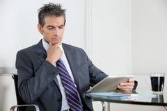 Созерцательный бизнесмен используя таблетку цифров внутри Стоковое фото RF