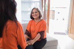 Созрейте азиатская женщина делите ее рассказ с дочерью стоковые изображения