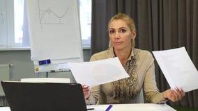 Созрейте бизнес-леди смотря смущенный пока рассматривающ документы стоковое фото rf