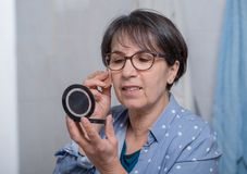 Созрейте женщина делая состав пока смотрящ малое зеркало Стоковые Изображения