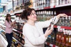 Созрейте и молодые женщины выбирая бутылку водочки стоковые изображения rf