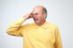 Созрейте кавказский человек в желтом отвращении tshirtwith на его щипках стороны обнюхайте стоковые фотографии rf