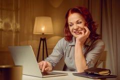 Созрейте красная женщина волос работая на компьтер-книжке пока сидящ на таблице Стоковое Фото