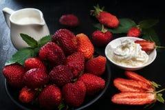 Созрейте красные клубники и сливк на черной таблице Молочник, клубники в плетеных корзинах, разбросал ягоды Стоковые Фото