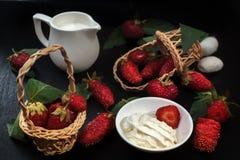 Созрейте красные клубники и сливк на черной таблице Молочник, клубники в плетеных корзинах, разбросал ягоды Стоковые Изображения RF