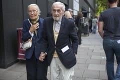 Созрейте модно одетые пары идя вдоль улицы стоковое фото