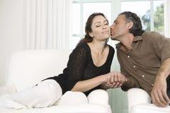 Созрейте пары целуя в живущей комнате. Стоковое Фото