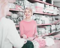 Созрейте покрывала женского продавца предлагая к молодой женщине в домашнем t стоковая фотография