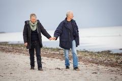 Созрейте счастливые пары идя на пляж в осени стоковая фотография