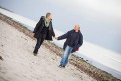 Созрейте счастливые пары идя на пляж в осени стоковые фотографии rf