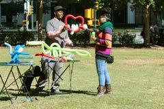 Создатель воздушного шара вручает женским раздувное клиента сформированное сердцем Стоковые Фотографии RF