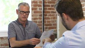 Соискатель более старого бизнесмена интервьюируя мужской в офисе видеоматериал