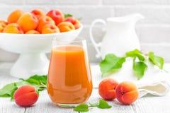 Сок абрикоса и свежие фрукты с листьями на белом деревянном столе Стоковые Фотографии RF