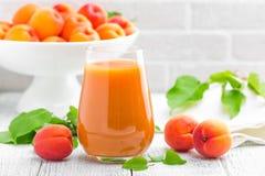 Сок абрикоса и свежие фрукты с листьями на белом деревянном столе Стоковые Изображения RF