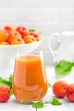 Сок абрикоса и свежие фрукты с листьями на белом деревянном столе Стоковая Фотография
