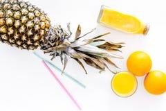Сок ананаса в стекле и бутылке около всех ананаса, апельсинов и tubule на белом взгляд сверху предпосылки Стоковое Изображение