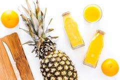 Сок ананаса в стеклянной бутылке около всех ананаса и апельсинов на белом взгляд сверху предпосылки Стоковые Фото