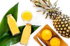 Сок ананаса в стеклянной бутылке около всех ананаса и апельсинов на белом взгляд сверху предпосылки Стоковое Изображение RF