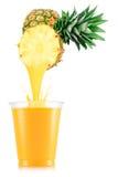 Сок ананаса лить вне от плодоовощ в пластичную чашку Стоковое Фото