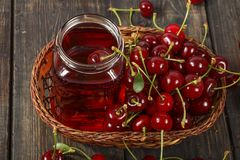 Сок вишни и свежие вишни на деревянной предпосылке Свежий сок вишни в стекле Свежая вишня на деревянном столе Стоковое фото RF