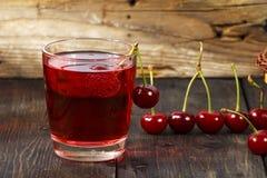 Сок вишни и свежие вишни на деревянной предпосылке Свежий сок вишни в стекле Свежая вишня на деревянном столе Стоковые Фото