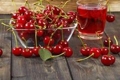 Сок вишни и свежие вишни на деревянной предпосылке Свежий сок вишни в стекле Свежая вишня на деревянном столе Стоковое Изображение RF