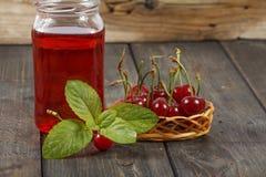 Сок вишни и свежие вишни на деревянной предпосылке Свежий сок вишни в стекле Свежая вишня на деревянном столе Стоковые Изображения