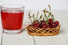 Сок вишни и свежие вишни на деревянной предпосылке Свежий сок вишни в стекле Свежая вишня на деревянном столе Стоковая Фотография RF