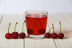Сок вишни и свежие вишни на деревянной предпосылке Свежий сок вишни в стекле Свежая вишня на деревянном столе Стоковое Фото