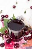 Сок вишни на деревянной предпосылке Стоковые Изображения RF