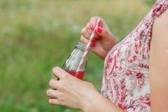 Сок вытрезвителя женщины выпивая на улице стоковое изображение