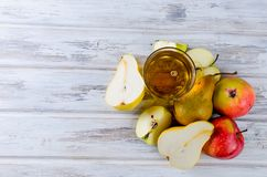 Сок в стеклянном и зрелые яблоки и груши на деревянном столе Стоковое Фото