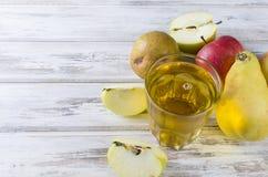 Сок в стеклянном и зрелые яблоки и груши на деревянном столе Стоковые Фото