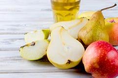 Сок в стеклянном и зрелые яблоки и груши на деревянном столе Стоковые Фотографии RF